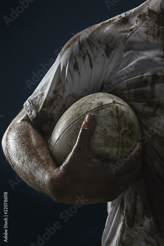 Fotografiet  Rugby player hands with ball on dark background. Close up
