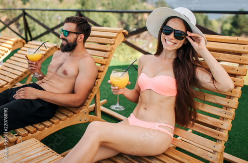 Nice picture of girl and guy sitting on sunbeds Canvas Print