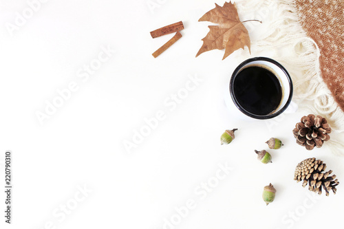 Fall feminine styled composition. Breakfast scene with enamel mug, coffee, dried leaf, cinnamon and plaid. White table background. Autumn cozy still life. Flat lay, top view.