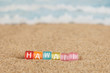 Word HAWAII from multicolored cubes in the sand on the background of beach and sea