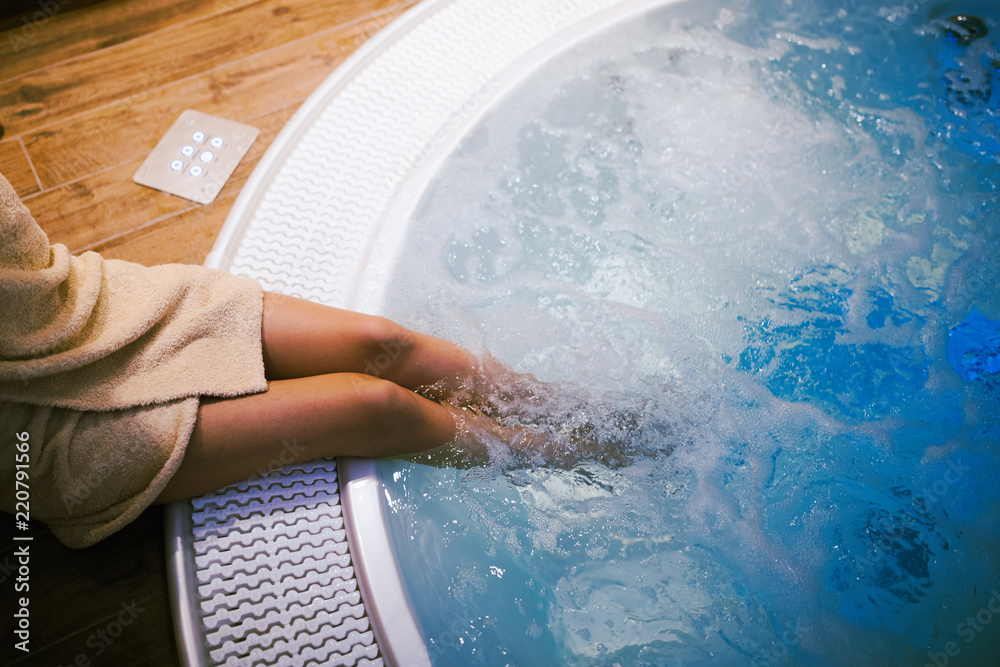 Woman entering jacuzzi in spa resost