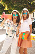 Two young stylish smiling hippie brunette and blond women models in summer hipster clothes with penny skateboard posing on the street background. Surprise face, emotions