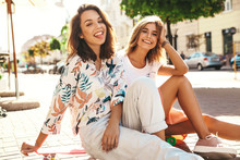 Two Young Stylish Smiling Hippie Brunette And Blond Women Models In Summer Sunny Day In Hipster Clothes Sitting On Penny Skateboard On The Street Background. Showing Tongue