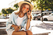 Portrait of beautiful cute blond teenager model in summer hipster clothes sitting on the street background and listening music on her mobile phone