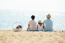 Back View Portrait Of Blissful Modern Family Sitting On Beach And Looking At Sea Enjoying Picnic During Summer Vacation, Copy Space