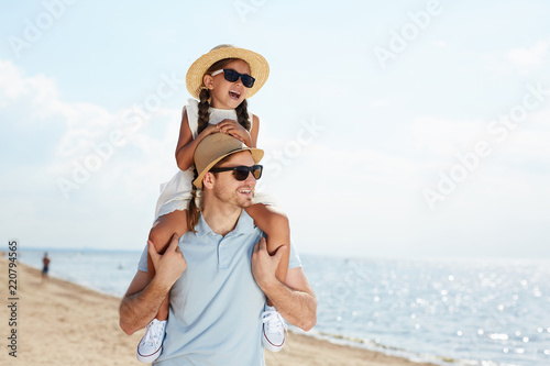 Waist up portrait of modern young man holding daughter on shoulders and walking on beach along sea enjoying Summer vacation, copy space