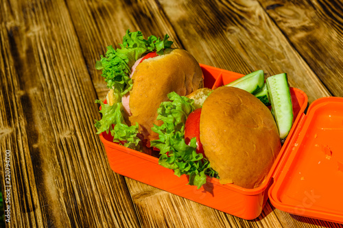 Foto op Plexiglas Assortiment Hamburgers with lettuce in lunchbox on wooden table