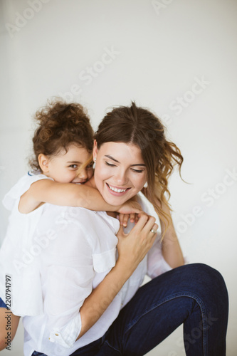 Fotografia  Cute little daughter happily hugging beautiful mother while spen