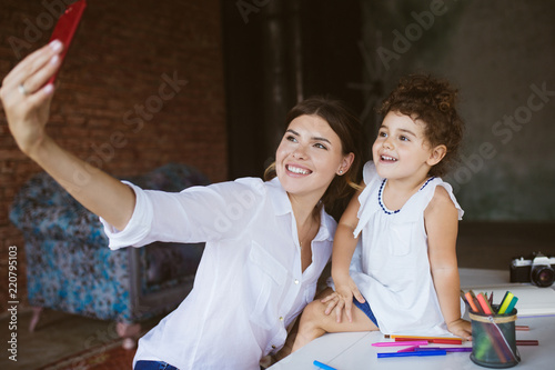 Fotografia  Beautiful smiling mother and cute baby daughter happily taking p