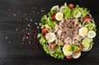 Salad with tuna, anchovies and vegetables. Mediterranean food. The background is black. Top view. Copy space. Horizontal shot.