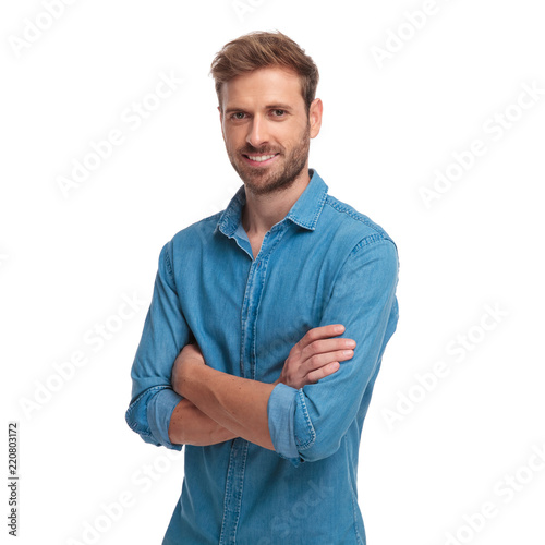 Obraz young smiling casual man standing with hands crossed - fototapety do salonu