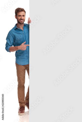 Obraz happy casual man poiting finger at a blank board - fototapety do salonu