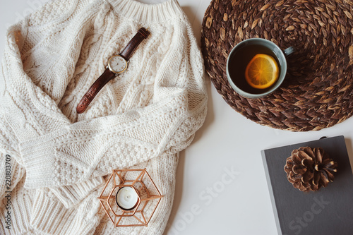 Photo Stands Autumn fall or winter cozy still life set. Warm knitted sweater, cup of tea with lemon, and book with pine cone on white background. Hygge concept.