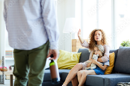 Fotografie, Obraz  Young woman saying her husband with bottle of wine to go away and stop drinking