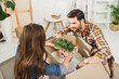 partial view of young couple unpacking cardboard boxes together at new home, moving home concept
