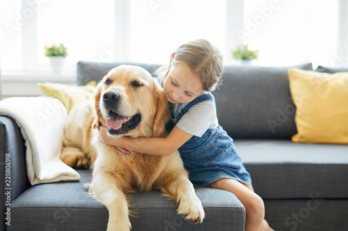 Fotografía  Little child embracing her labrador pet while both relaxing on sofa at home