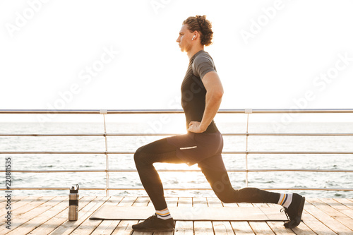 Canvas Print Portrait of a healthy sportsman doing lunges exercises