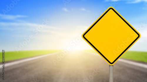 Cuadros en Lienzo Blank yellow road sign or Empty traffic signs on blurred asphalt road with colorful light background