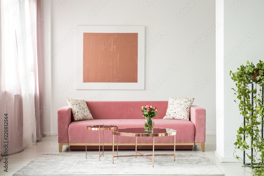 Fototapeta Pillows on pink sofa in white apartment interior with painting and flowers on copper table. Real photo