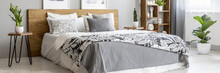 Natural Wooden Furniture And A Cozy, Double Bed With Stylish Graphic Sheets And Pillows In A Gray Bedroom Interior With Plants