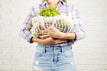Young Woman In Plaid Shirt, Jeans Skirt With Bag Of Mixed Fruit, Vegetables: Corn Cob, Tomato, Pepper, Lettuce, Pear & Apple. Zero Waste Concept. Brick Wall Copy Space Background, Wood Floor, Close Up