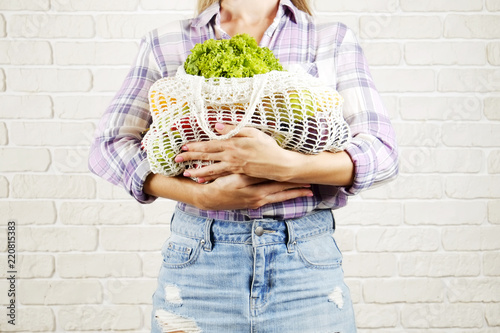 Fotografía  Young woman in plaid shirt, jeans skirt with bag of mixed fruit, vegetables: corn cob, tomato, pepper, lettuce, pear & apple