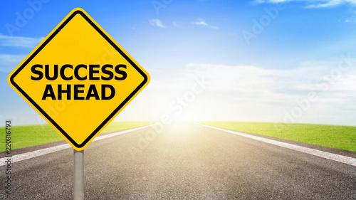 Fotografia, Obraz Success ahead road sign on asphalt road with colorful light background