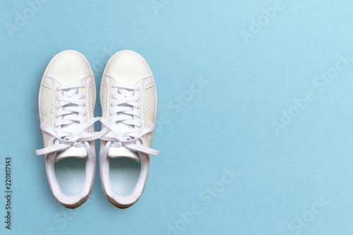 Obraz na płótnie White sneakers isolated on blue background