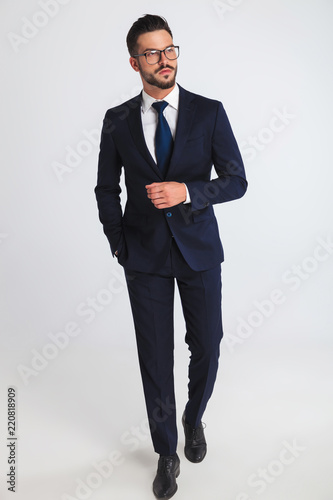 Fotomural relaxed businessman wearing glasses and navy suit walking