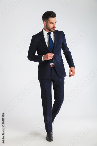 young businessman walking and buttoning his navy suit Fototapeta
