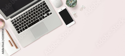 bright feminine banner / header with a stylish workspace with laptop computer, smartphone, modern office accessories and a small succulent on a blush table, top view / flat lay