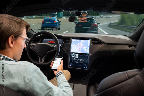 Cuadros en Lienzo A man reads news online in a smartphone while his car is driven by an autopilot