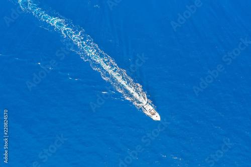 Luftaufnahme eines Motorbootes welches über türkis blaues Meer fährt