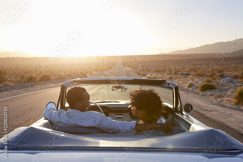 Obraz Rear View Of Couple On Road Trip Driving Classic Convertible Car Towards Sunset - fototapety do salonu
