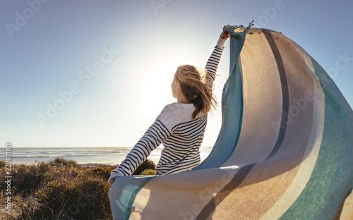 Obraz Woman standing near the sea holding a drape - fototapety do salonu