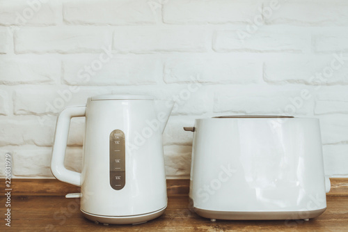 white kettle and toaster mockup stand on a wooden table on a white brick wall background