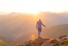 Athletic Woman Standing On A Mountain Ridge At Sunrise, Gastein, Salzburg, Austria