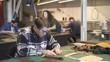 Young male technician measuring artificial leather details in sewing studio. Craftsman in round glasses working on the pieces of cloth at the table and his collegues doing their jobs on the background