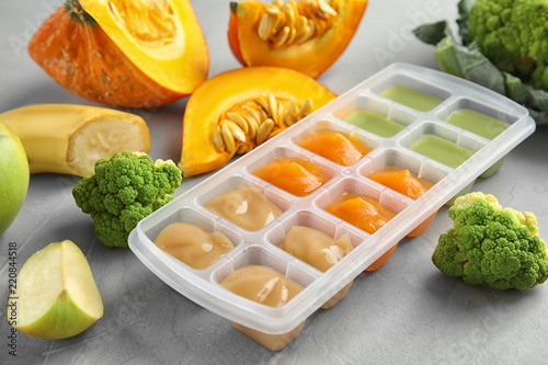 Ice cube tray with healthy baby food on table