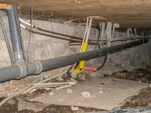 Suspended Foundation Under Old House Is Often Called Crawl. Pipes For Drain, Sewer, Water And Electricity.