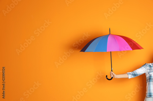 Woman holding beautiful umbrella on color background with space for design Fototapet