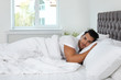 Young man lying in bed with soft pillows at home