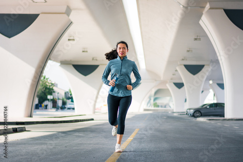 Girl running bellow the bridge in urban area Wallpaper Mural