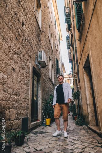 young stylish man walking by tight Kotor street. Montenegro
