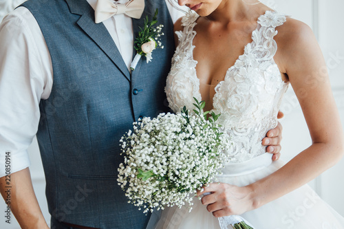 bride and groom together holding wedding bouquet Fototapete