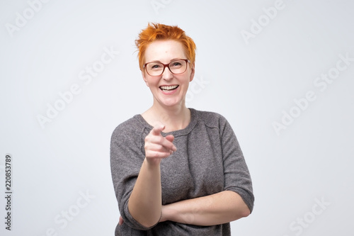 Fotografía Happy mature fashion woman with red hair posing for the camera while pointing at you