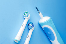 Modern Electric Toothbrush And Spare Heads On Blue Background