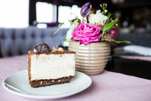 Creamy Cheesecake With Chocolate Cookies And Cream Biscuits. Oreo Cake And A Beautiful Vase With Flowers On The Table. A Beautiful Bouquet Of Flowers From Roses And Tulips.