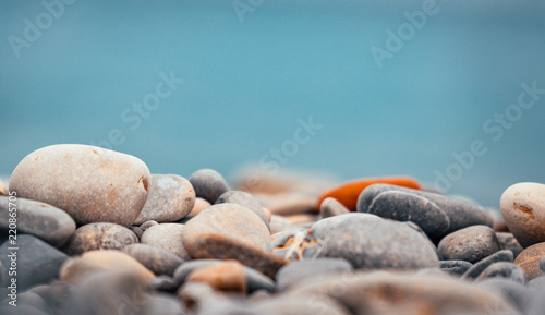Poster de jardin Zen pierres a sable Close up of pebble and stone rock beach with blue ocean