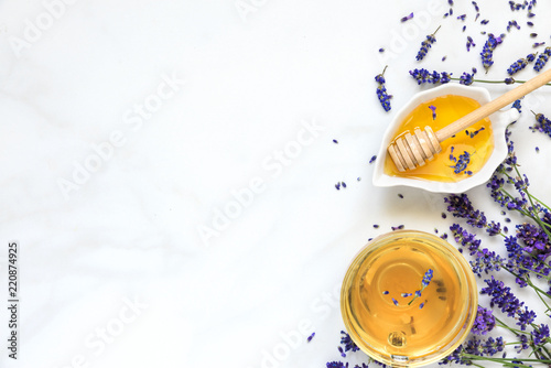 cup of lavender tea with honey and fresh flowers over white marble table. herbal drink. top view